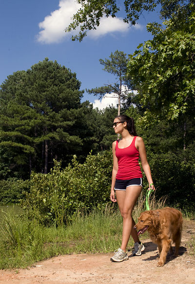 A+young+woman+walking+her+dog+outdoors